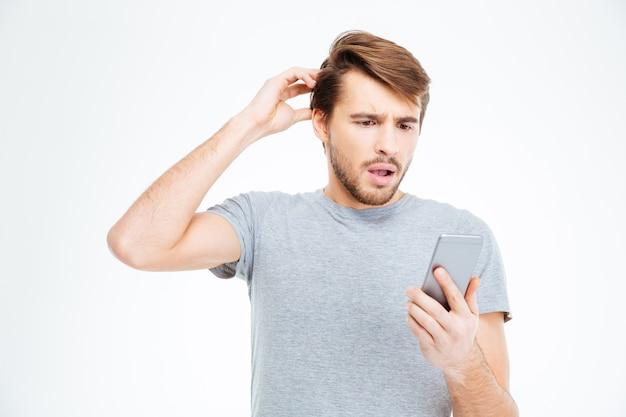Erstaunter mann, der auf dem smartphone lokalisiert auf einem weißen hintergrund schaut