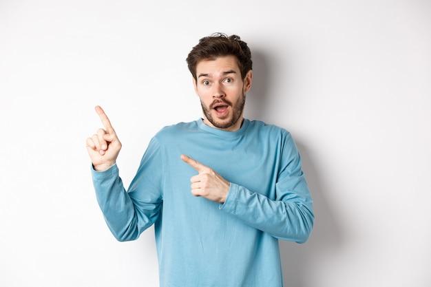 Erstaunter mann, der fantastisches promo-angebot zeigt, finger auf logo der oberen linken ecke zeigt und aufgeregt aussieht, produkt empfehlen, weißer hintergrund.