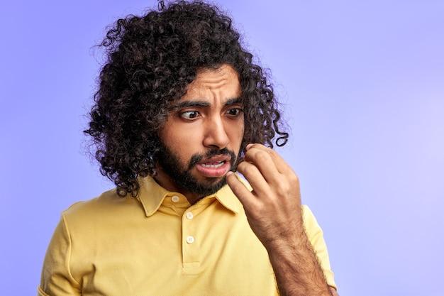 Erstaunter mann, der sein langes lockiges haar betrachtet, will isoliert über lila raum schneiden