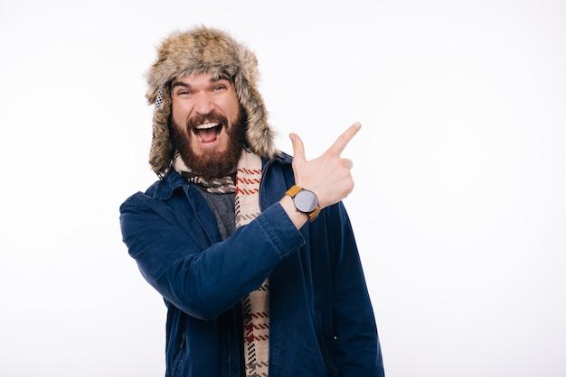 Erstaunter mann, der winterkleidung trägt und auf copyspace zeigt