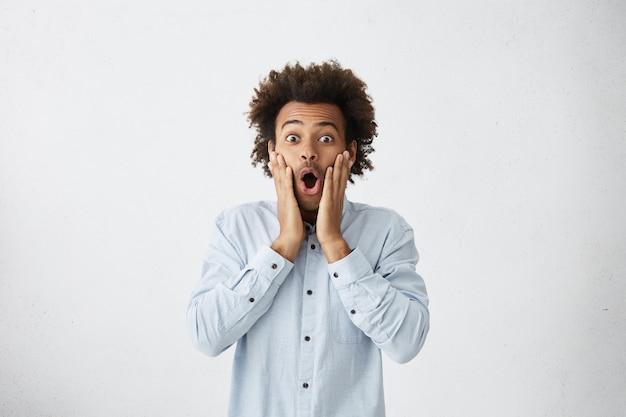 Erstaunter mann gemischter abstammung mit afro-haarschnitt, der seine wangen berührt und mit abgehörten augen aussieht