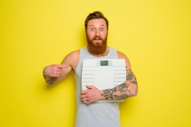 Erstaunter mann mit bart und tattoos hält eine elektronische waage