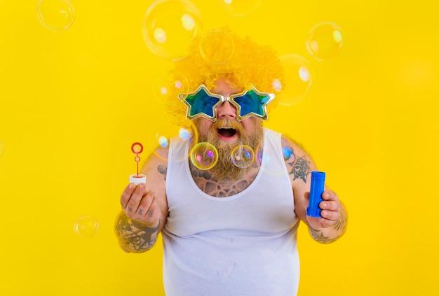 Erstaunter mann mit gelber perücke im kopf spielt mit seifenblasen