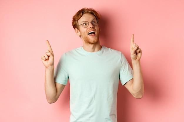 Erstaunter rothaariger mit brille, der das sonderangebot anschaut und mit erstaunten fingern nach oben zeigt ...
