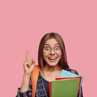 Erstaunter student, der mit brille gegen die rosa wand posiert