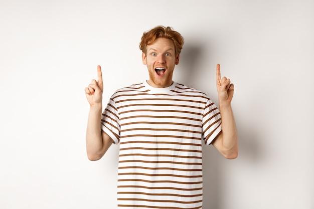 Erstaunter und aufgeregter rothaariger mann, der beförderung auscheckt, finger zeigt und logo zeigt, kamera anstarrt, über weißem hintergrund steht.