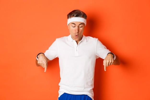 Erstaunter und aufgeregter sportler mittleren alters in fitnesskleidung