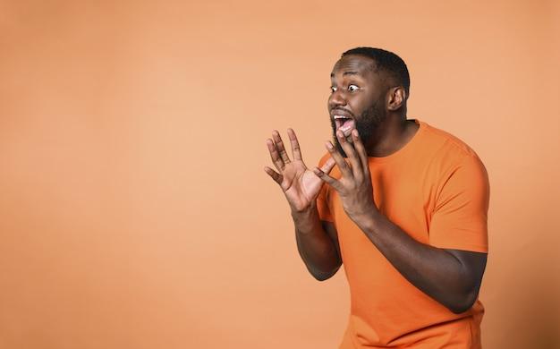 Erstaunter und schockierter ausdruck eines jungen über der orangefarbenen wand