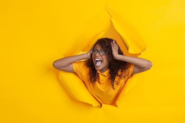 Erstauntes geschrei. fröhliche afroamerikanische junge frau in zerrissenem gelbem papierhintergrund, emotional, ausdrucksstark. aufbruch, durchbruch. konzept der menschlichen emotionen, gesichtsausdruck, verkauf, anzeige.