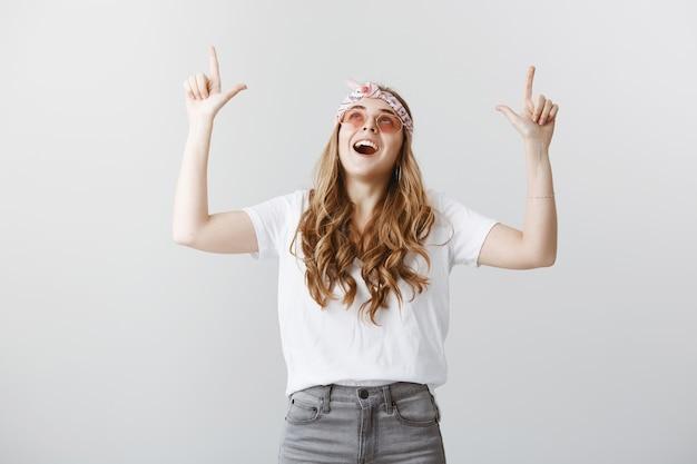 Erstauntes glückliches blondes mädchen in der sonnenbrille, die finger zeigt und zeigt