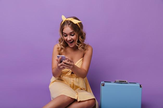 Erstauntes hübsches mädchen mit koffer, der telefonische nachricht liest. porträt der freudigen lockigen dame mit blauem koffer, der ihr smartphone betrachtet.
