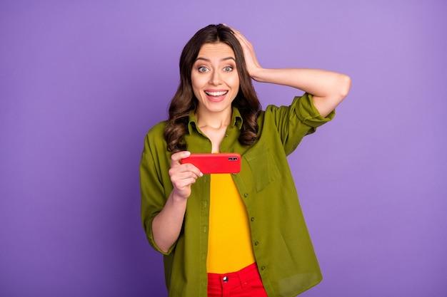 Erstauntes mädchen, das handy benutzt, um soziale netzwerk-videospiele zu spielen, beeindruckt schnelle internetverbindung berühren hände kopf tragen stil stilvolles outfit isoliert lila farbhintergrund