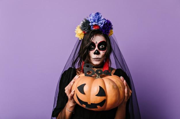 Erstauntes mädchen mit halloween-make-up, das gemalten kürbis hält. porträt der dunkelhaarigen brünette im schwarzen outfit.