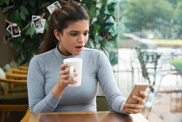 Erstauntes mädchen trinkt kaffee und surft netz