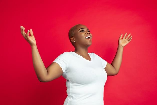 Erstauntes porträt der afroamerikanischen jungen frau auf rotem hintergrund