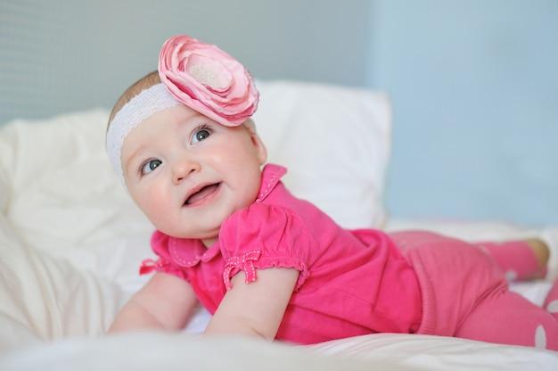 Erstauntes süßes kleines baby mit molligen wangen, die rosa kleidung und bandblume tragen