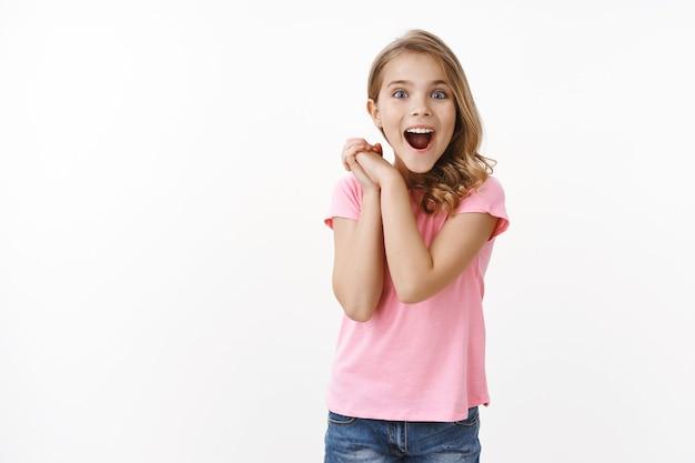 Erstauntes süßes kleines kind sieht wundervolle sache, klammert sich freudig aufgeregt an die hände und sieht die kamera mit bewunderung aus, lächelt breit amüsiert, schaut unterhalten und überrascht, erhält ein cooles geschenk, weiße wand