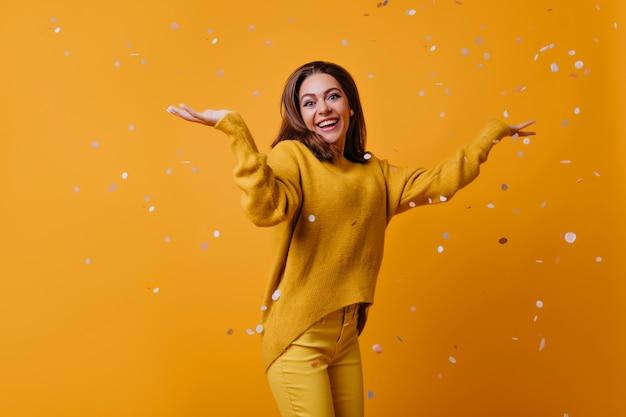 Erstauntes süßes mädchen mit dunklem haar, das auf gelber wand tanzt. ansprechende stilvolle frau, die konfetti herauswirft.