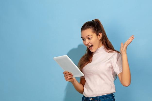 Erstauntes teenager-mädchen mit tablette