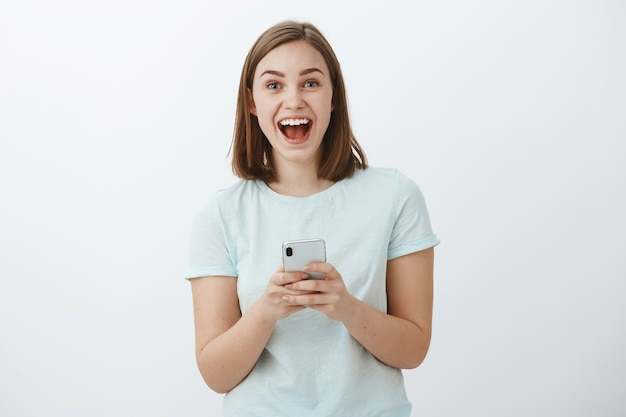 Erstauntes und aufgeregtes attraktives junges europäisches weibliches modell, das breit von den großen nachrichten lächelt, die über das internet erhalten werden, das smartphone hält, das begeistert und entzückt schaut, das gegen weiße wand aufwirft