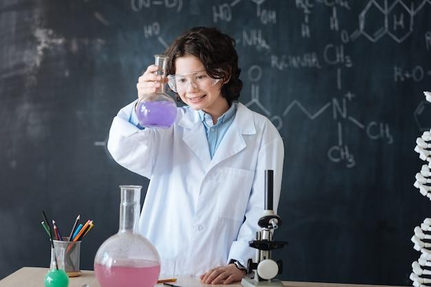 Erste erfolge feiern. ein zufriedener, inspirierter wissenschaftler, der im labor steht und den chemieunterricht genießt, während er am wissenschaftsprojekt teilnimmt und sein glück ausdrückt