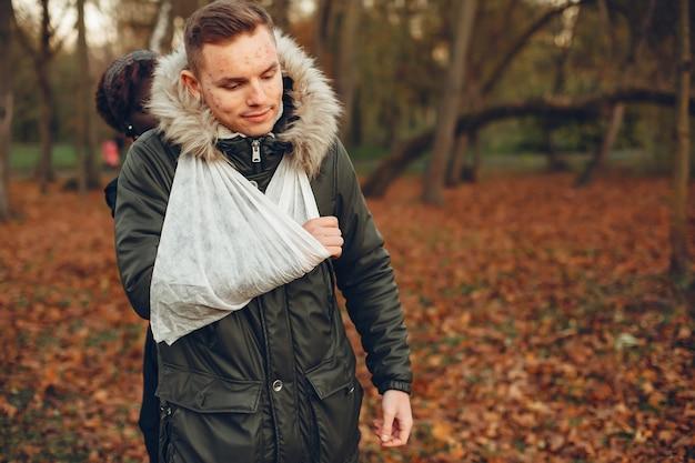 Erste hilfe im park leisten. afrikanisches mädchen bandagierte die hand des jungen. verwundeter mann im park