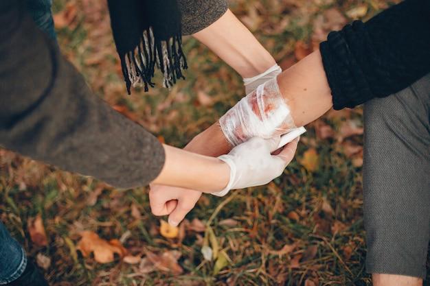 Erste hilfe im park leisten. mann bandagierte verletzten arm. guy hilft einem freund.