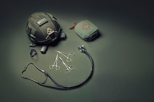 Erste-hilfe-kasten, phonendoskop, eine schere mit helm liegen auf grünem grund. draufsicht. militärmedizinisches konzept