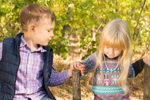 Erste liebe - kleine lieblinge mit einem niedlichen kleinen blonden mädchen, das zärtlich die hand eines hübschen kleinen jungen nimmt, während sie draußen auf dem land zusammenstehen