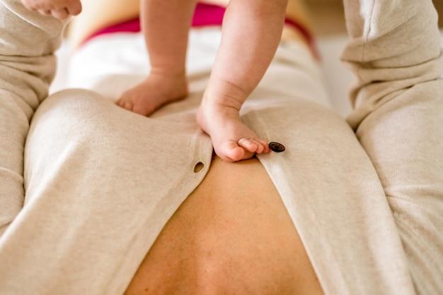 Erste schritte eines babys auf der brust seiner mutter.