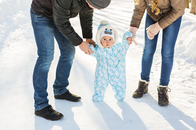 Erste schritte. kleines baby, das laufen lernt. mutter und vater mit kleinkind im winterpark