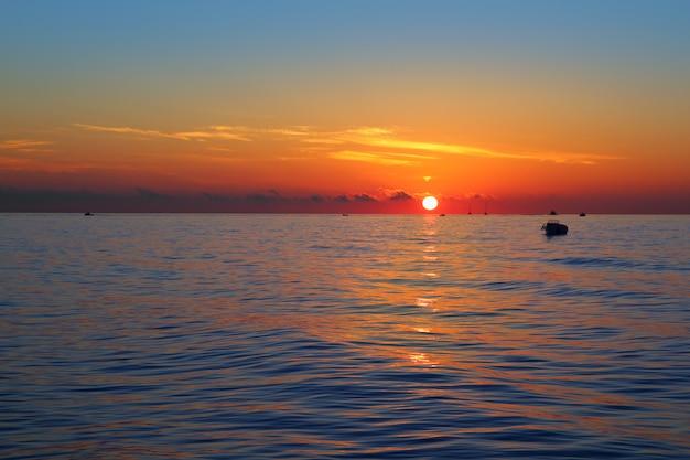 Erste sonnenorange des meerblicksonnenaufgangs im blauen meer