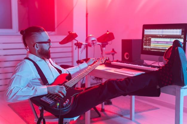 Erstellen sie musik und ein aufnahmestudio-konzept - bärtiger lustiger gitarrist, der e-bass aufnimmt