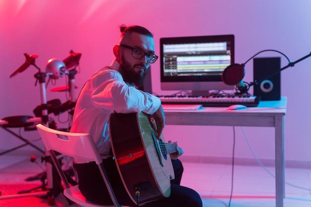 Erstellen sie musik und ein aufnahmestudio-konzept - bearded man-gitarrist, der e-gitarren-tracks aufzeichnet