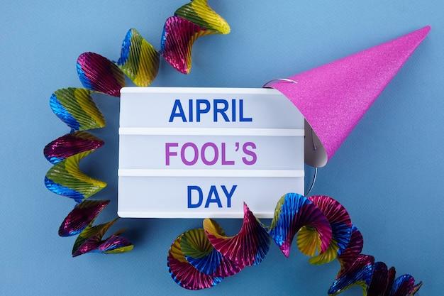 Erster april. überraschungssymbol. schnürsenkel zusammengebunden auf blauem hölzernem hintergrund. aprilscherz.