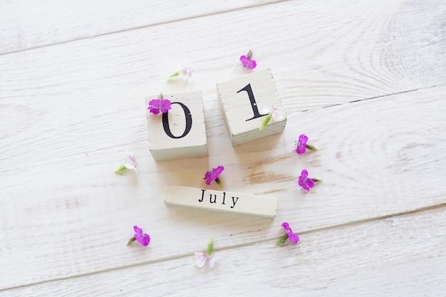 Erster juli-tag, bunter hintergrund mit kalender, blumen