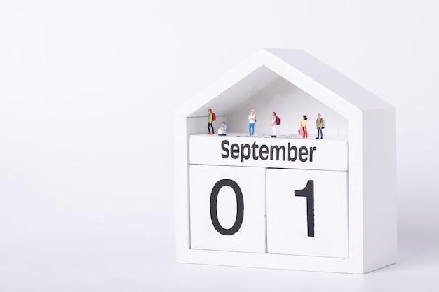 Erster schultag. figuren von studenten, die auf einem kalender stehen, der den ersten september darstellt