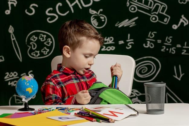 Erster schultag. junge von der grundschule. zurück zur schule. kleiner junge sammelt schulrucksack zur schule. kind von der grundschule.