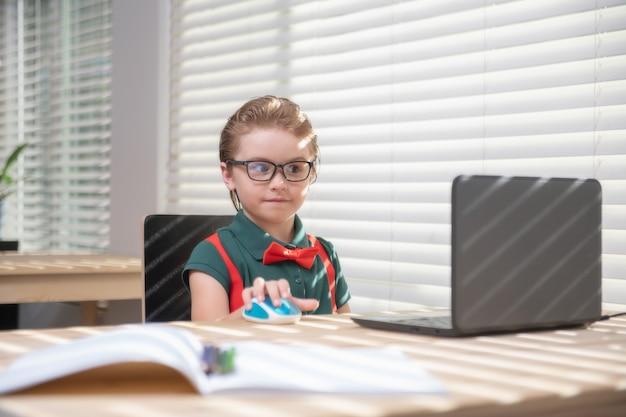 Erster schultag. nettes kleines kind mit laptop-computer, computer studieren.