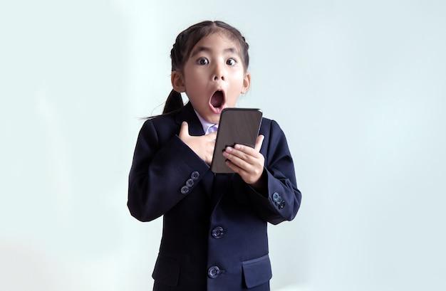 Erstickendes asiatisches kind mit handy in business-uniform-suite. zielgruppe der marketing-persona der neuen generation mit business-suite-kostüm