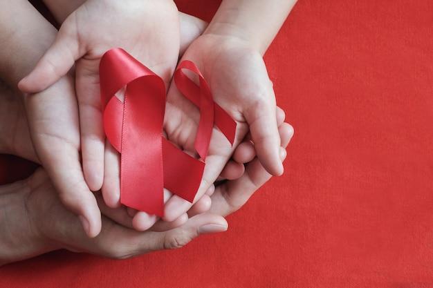 Erwachsen- und kinderhände, die rotes band auf rotem hintergrund halten