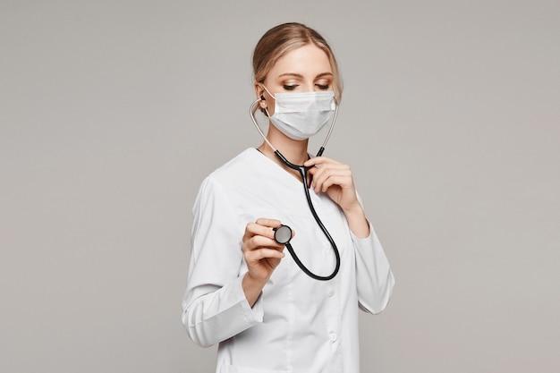 Erwachsene ärztin in medizinischer uniform und schützender gesichtsbedeckung posiert mit einem stethoskop auf grau