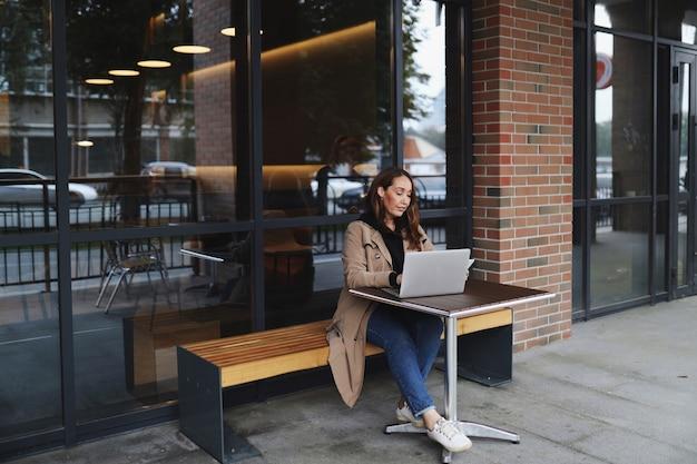Erwachsene arbeitende frau in der freizeitkleidung unter verwendung des laptops