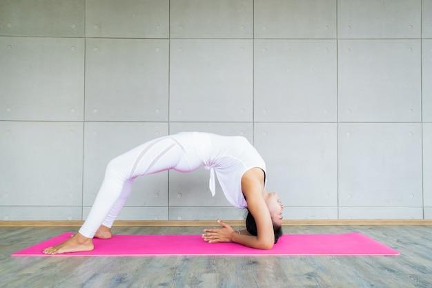 Erwachsene asiatin, die eine yogaübung im übungsraum in ihrem haus tut.