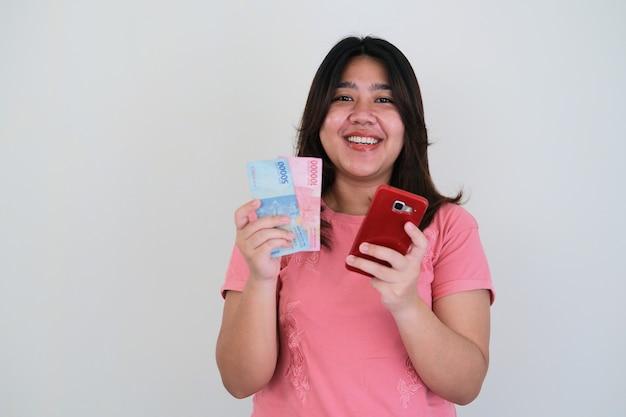 Erwachsene asiatische frau, die glücklich lächelt, während sie papiergeld und handy hält