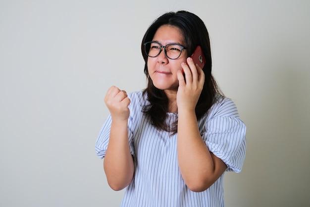 Erwachsene asiatische frau, die wütenden gesichtsausdruck zeigt, während sie einen telefonanruf beantwortet