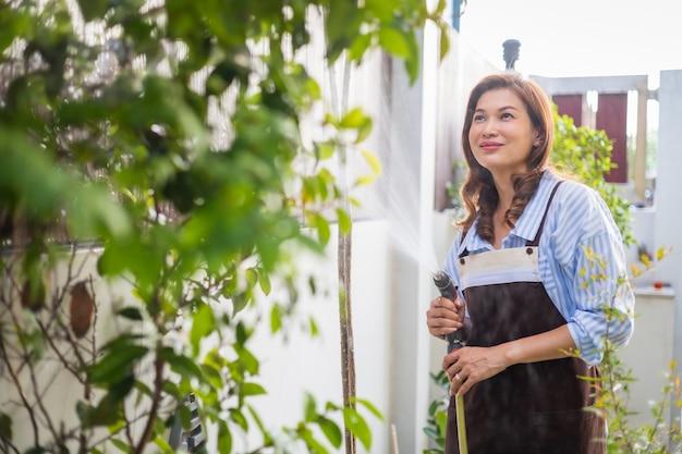 Erwachsene asiatische hausfrau, die schürze trägt, die wassersprüher hält und kleine pflanze im kleinen hinterhof-hausgarten mit glück gießt.