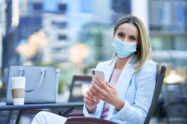 Erwachsene attraktive frau in maske mit smartphone und entspannung in der stadt