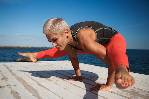Erwachsene blonde frau mit kurzem haarschnitt übt yoga auf dem pier vor dem hintergrund des meeres und des blauen himmels