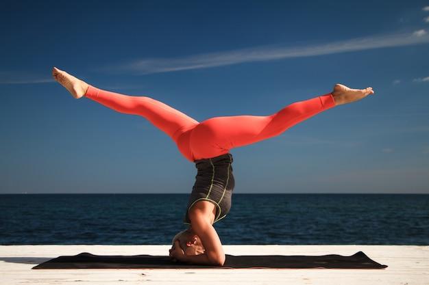 Erwachsene blonde frau mit kurzem haarschnitt übt yoga auf dem pier